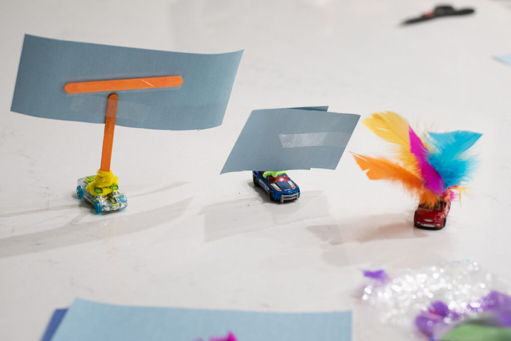 three wind powered cars made from toy cars